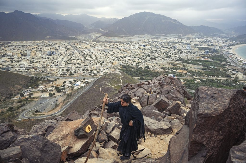 Woman in abaya climbing khor fakkan al rabi hiking trail overlooking hajar mountains