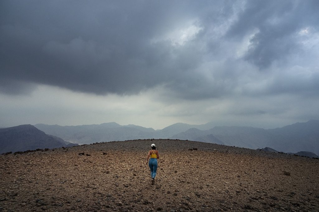 woman running on a mountain plateau on a cloudy evening in uae ras al kahimah