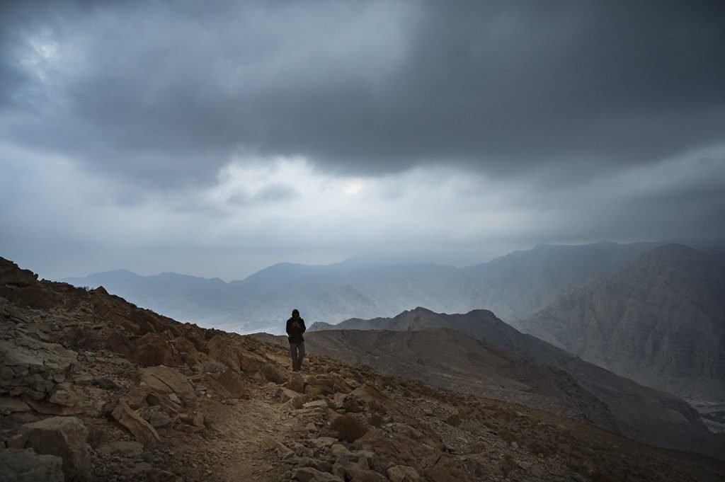 a man walking on the mountain trail in the uae on the cloudy evening after the sunset
