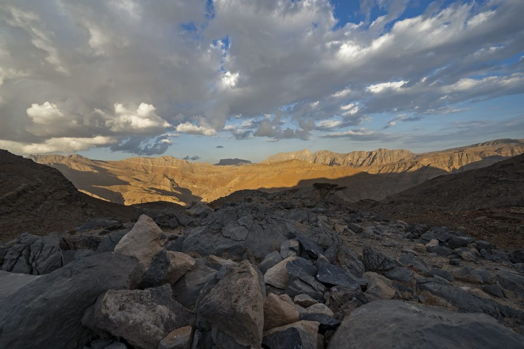 valley in uae mountains at sunset with clouds, big rock in the foreground