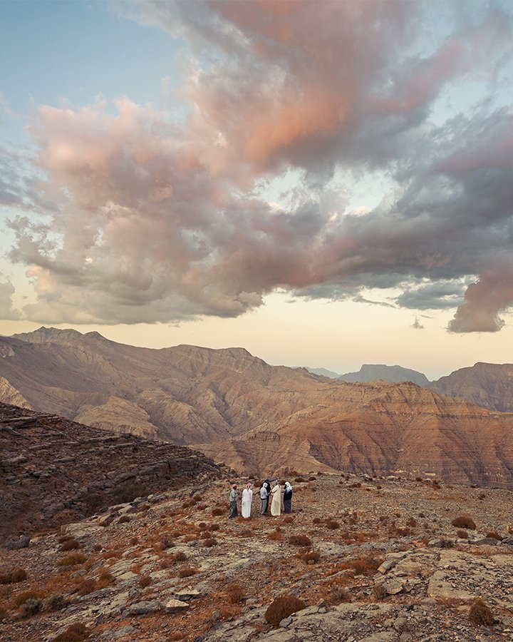 Cloudy Sunset at the top of the UAE mountains with a group of men standing