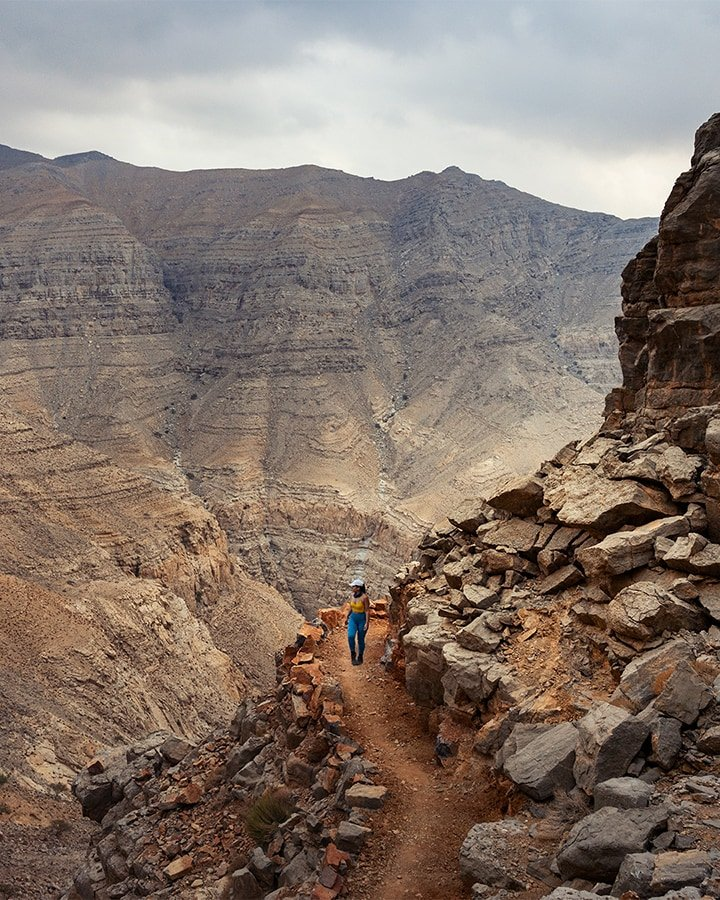woman on a hiking trail in uae mountains wearing blue leggings and white cap on a cloudy evening