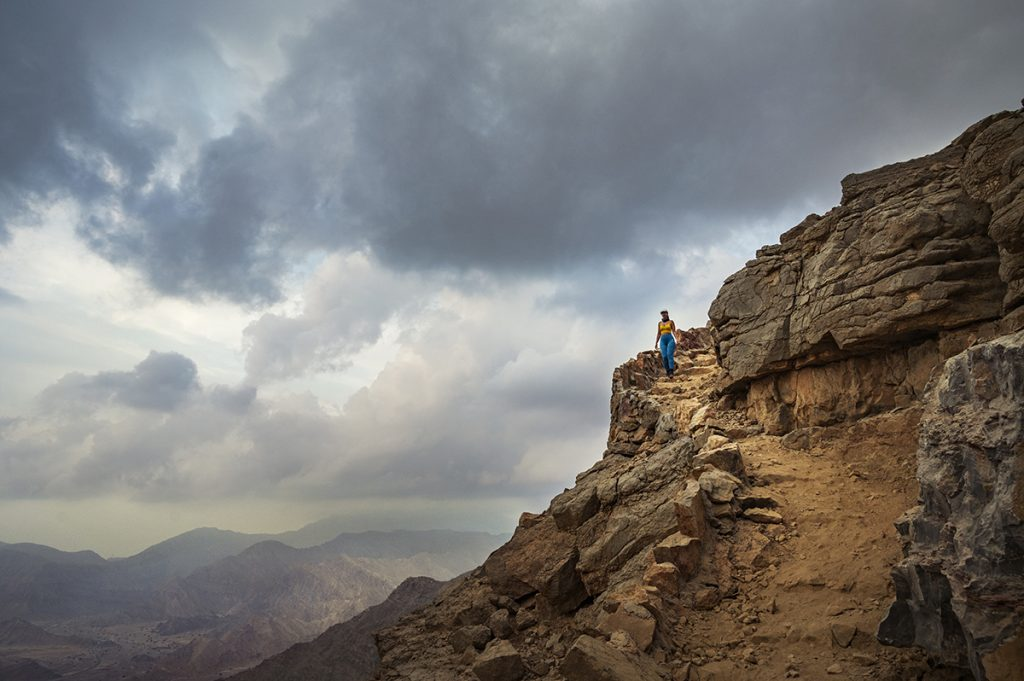 woman on a mountain trail in blue leggings at sunset in uae
