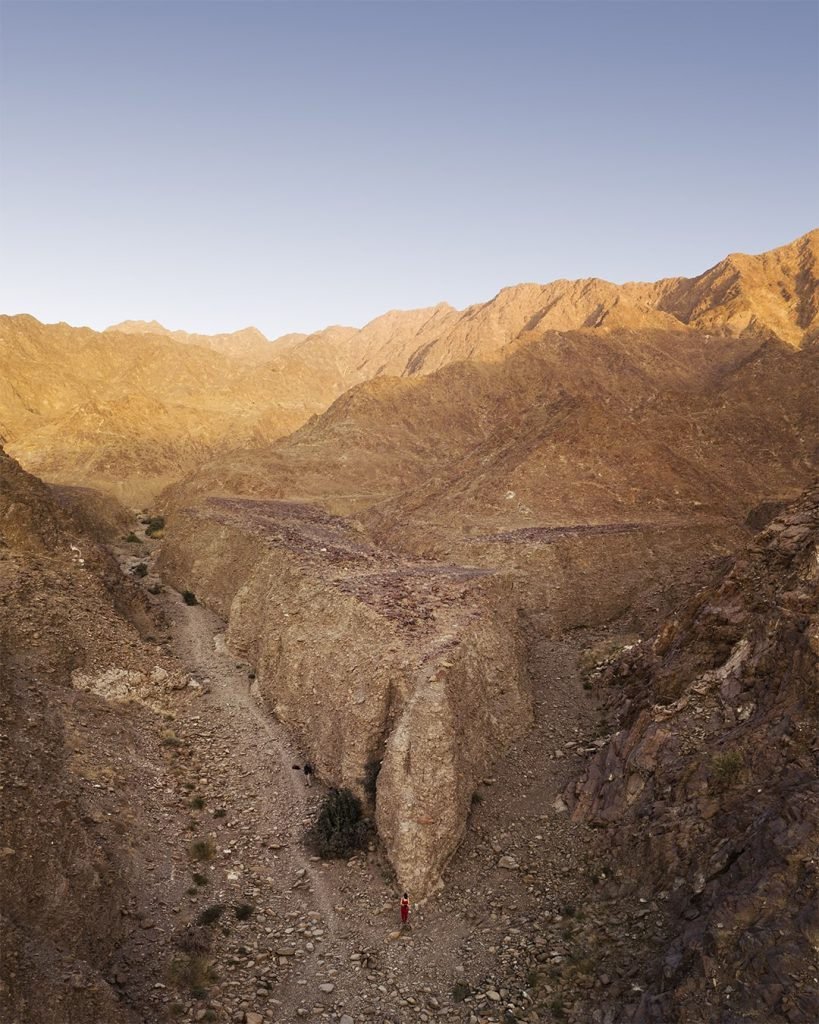 a deep ravine in hajar mountains at sunset