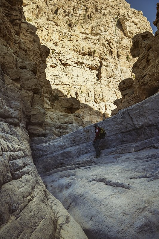 a man with a backpack in the gorge in wadi naqab uae