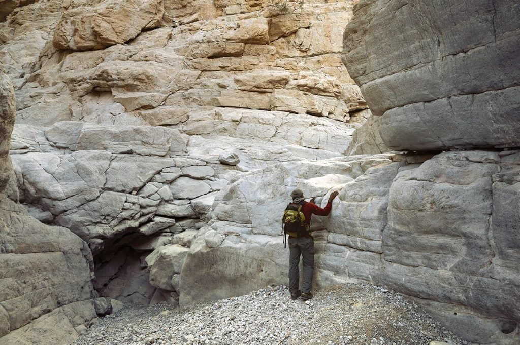 a man aiming to climb a white smooth rock in the gorge wadi naqab uae