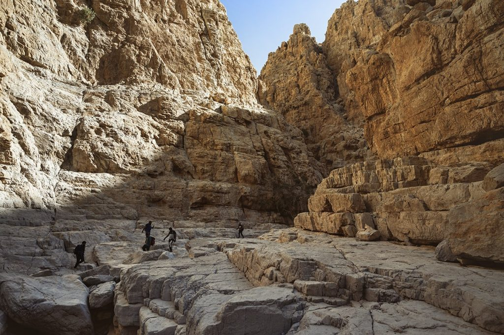 a group of people hiking in the gorge featuring ornage rocks around in wadi naqab uae