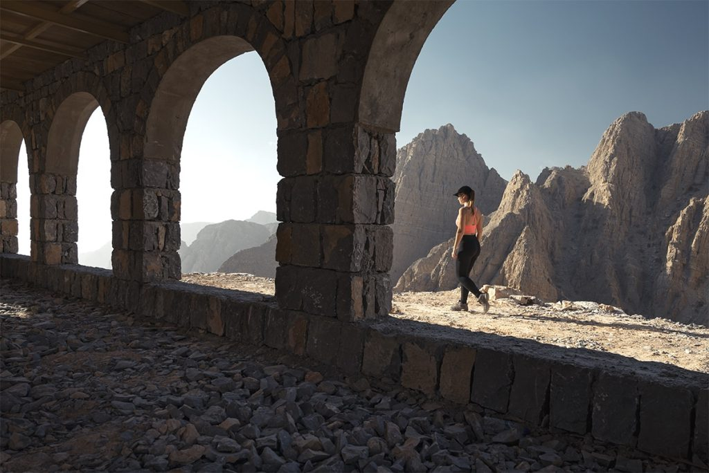 woman walking pass the building with arches with a mountain view in the backdrop