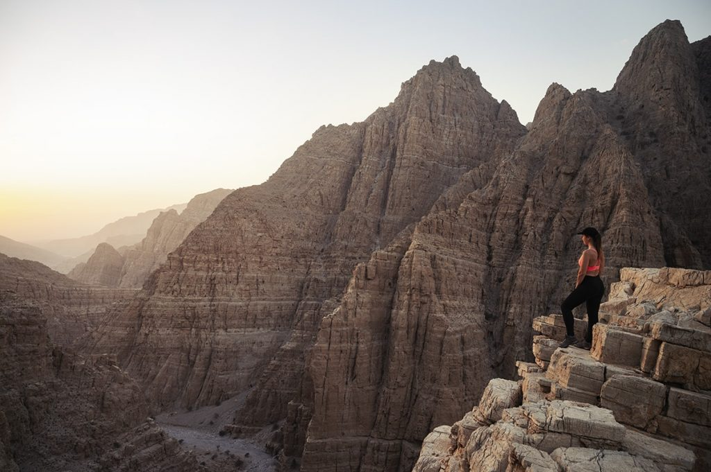 A woman standing at the edge of the mountain during the sunset