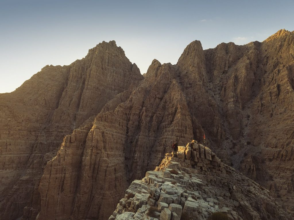 a man standing on the mountain ridge at sunset in ahajar mountains uae