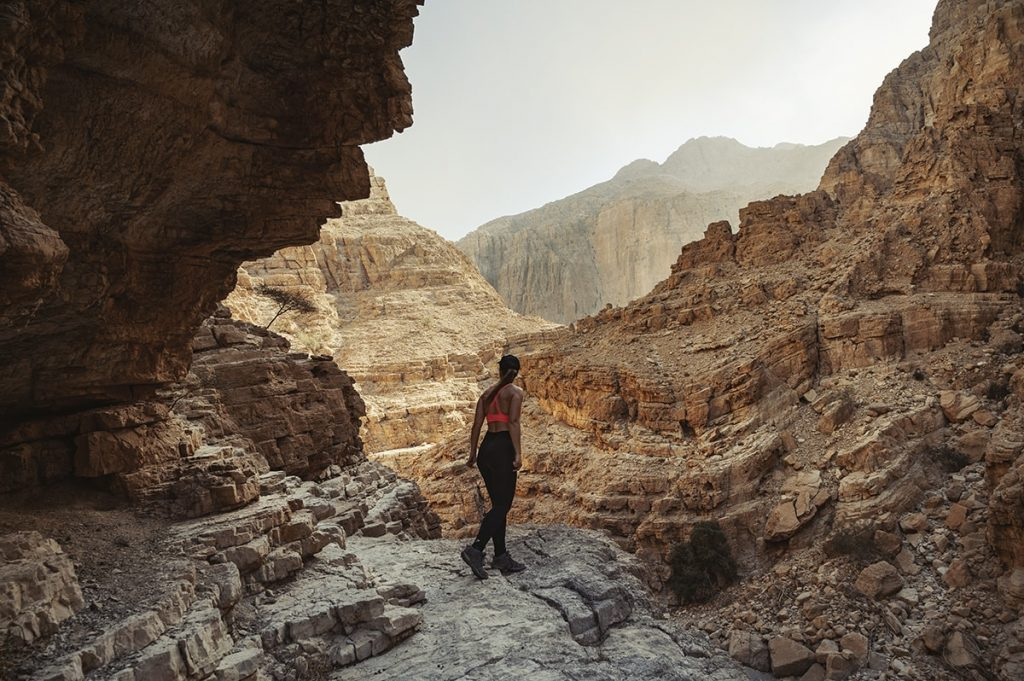 a woman looking out for the way on a rocky mountain trail in wadi naqab uae