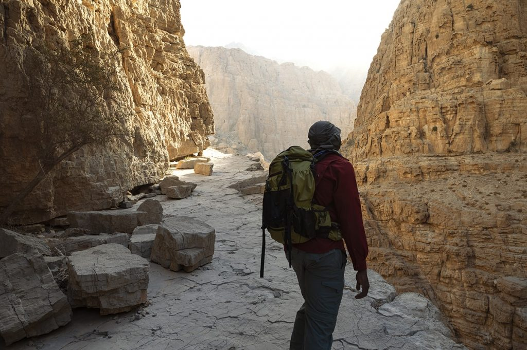 a man hiking on the mountain balcony in wadi naqab uae