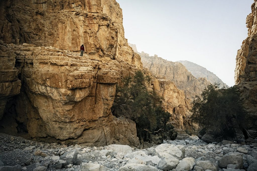 a man standing on the orange rock in the gorge uae