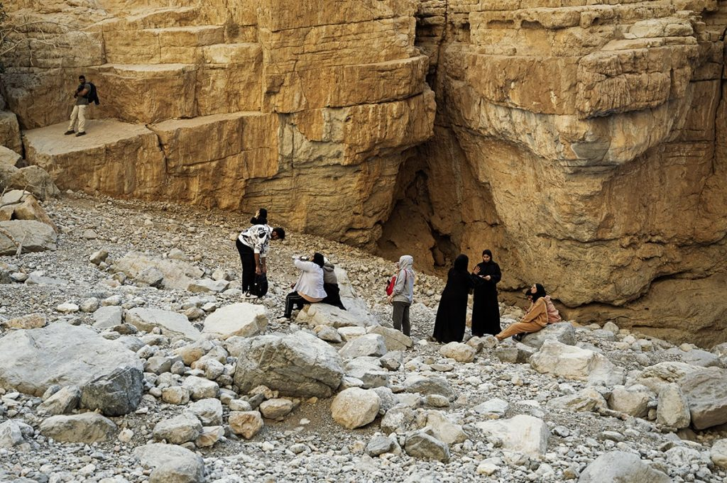 a group of people men and women some dressed in abayas hiking and sitting the gorge of wadi naqab uae
