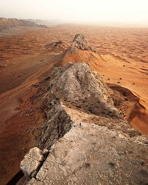 rugged rocks coming out of ornage sand dunes in mleiha uae