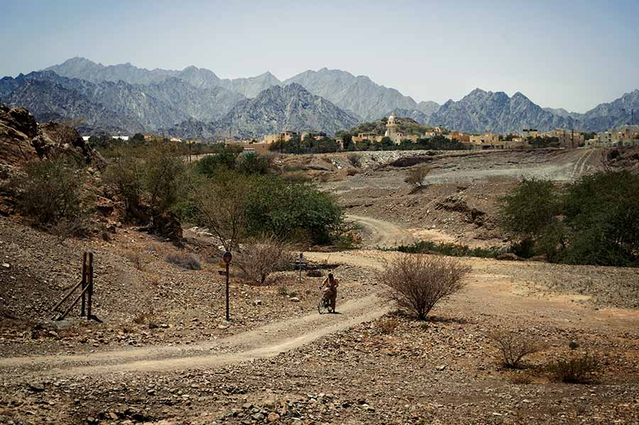 pakistani man on a bycicle riding through hatta mountain with town views in the backdrop