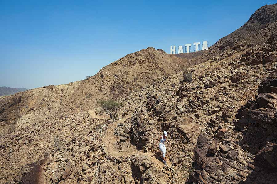 woman hiking at hatta mountain trails with hatta hollywood sign in the background